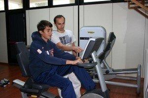 cyclette, riabilitazione post intervento e per recuperare il movimento dell'arto inferiore, caviglia, ginocchio, anca, rinforzo muscolare, flessione, attività aerobica, sport, atleti, infiammazione, rieducazione, fisioterapia, ragazzo, calciatore
